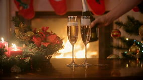 Closeup of hand pouring champagne in glasses on table at fireplace. Hand pouring champagne in glasses on table at fireplace stock video footage