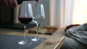 Closeup of hand pouring red wine in two glasses stock video footage