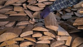 Closeup of hand in protective gloves puts wood in the warehouse. Closeup hand in protective gloves gently folds the firewood in the warehouse, wood for the stock video