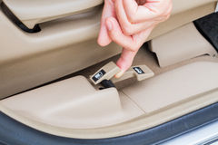 Closeup hand pulling fuel door open button in a car Stock Photo