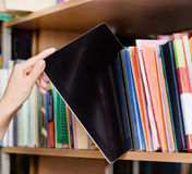 Closeup hand putting a tablet pc in the shelves in the library.  Stock Photos