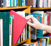 Closeup hand selecting book from a bookshelf Royalty Free Stock Images