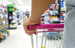 Closeup hand on shopping cart Royalty Free Stock Photo