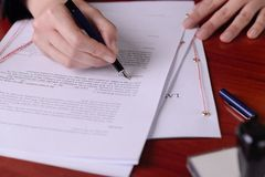 Closeup of a hand signing a last will by a pen. Royalty Free Stock Photos