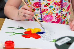 Closeup hand of small girl, holding brush, drawing colorful flowers Stock Photography