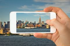 Closeup of a hand with smartphone taking a picture of Manhattan skyline, New York USA stock photography