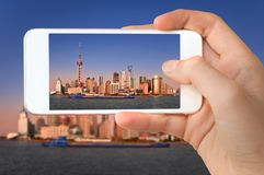 Closeup of a hand with smartphone taking a picture of Shanghai skyline and the Huangpu river China royalty free stock photo
