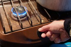 Hand starting a greasy gas stove. Closeup of a hand starting a greasy gas stove royalty free stock images