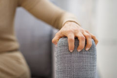 Closeup on hand of stressed woman sitting on divan. In living room Stock Photos