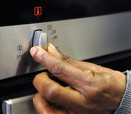Swiching on the oven Stock Images