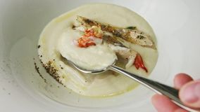 Closeup hand takes big spoon of fish cream soup decorated with prawns and spices