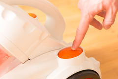 Closeup of a hand to turn on the vacuum cleaner. Man is unrecogn Stock Image