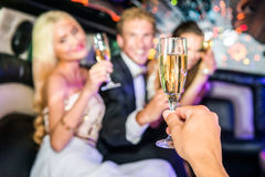 Closeup of hand toasting champagne flute with friends in limousi Royalty Free Stock Photos