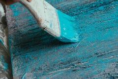 Closeup hand use brush paint white blue on wood surface Royalty Free Stock Image