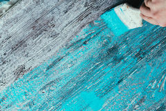 Closeup hand use brush paint white blue on wood surface Royalty Free Stock Photos