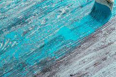 Closeup hand use brush paint white blue on wood surface Stock Photography