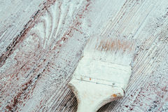 Closeup hand use brush paint white brown on wood surface.  Stock Photography