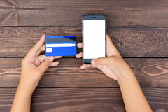 Closeup hand use phone and credit card on table top view Royalty Free Stock Photos