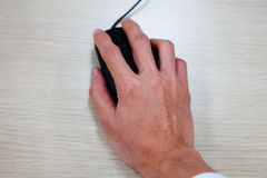 Closeup of hand using computer mouse. On wooden background Royalty Free Stock Photos