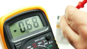 Closeup hand using digital multimeter to measure level of charge of a battery