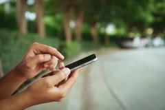 Closeup hand using phone on street royalty free stock photography