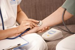 Closeup of hand using stethoscope on wrist. Closeup of nurse using stethoscope on wrist of senior woman Stock Photos