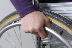Closeup of hand an wheel of wheelchair Stock Photography