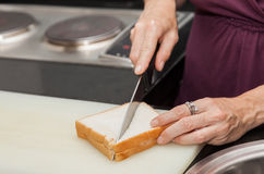 Closeup of a hand which a sandwich cut with the knife. Royalty Free Stock Images