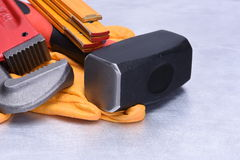 Closeup hand working tools pipe wrench and hammer Royalty Free Stock Photography