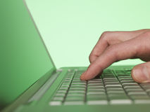 Closeup on a hand writing on a laptop Royalty Free Stock Image
