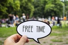 Text free time in a speech bubble. Closeup of the hand of a young caucasian man holding a signboard, in the shape of a speech bubble, with the text free time stock images