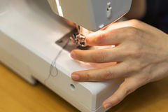 Closeup of hand a young woman, spends thread a sewing machine at Royalty Free Stock Photography