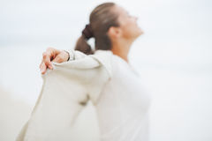 Closeup on hand of young woman in sweater on lonely beach Royalty Free Stock Photo