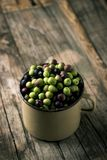 Arbequina olives from Spain. Closeup of a handled enamelware pot full of arbequina olives from Catalonia, Spain, on a wooden rustic table Stock Photo