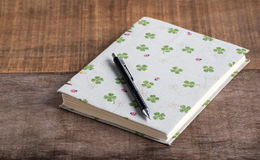 Closeup of handmade book and pen on wooden background Stock Photos