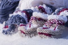 Closeup of handmade knitted baby booties in sunlight. Closeup with handmade knitted baby booties of warm wool in snowy winter sunlight Stock Images