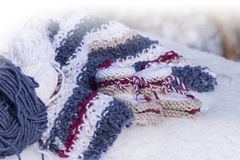Closeup of handmade knitted baby booties in snow. Closeup with handmade knitted baby booties of warm wool in snowy winter sunlight Royalty Free Stock Photos