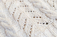 Closeup on handmade knitted fabric with white pattern copy space background Royalty Free Stock Photo