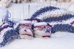 Closeup of handmade knitted woolen baby booties in snow. Closeup with handmade knitted baby booties of warm wool in snowy winter sunlight made with love Royalty Free Stock Images