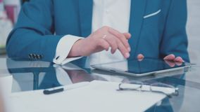 Closeup hands of businessman enjoying tablet. Gadgets. Close-up: the use of the tablet. A man at a business meeting uses a Tablet PC. Modern technologies. IPads stock footage