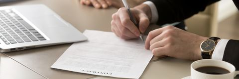 Closeup hands businessman sitting at desk accomplish meeting signing contract stock images