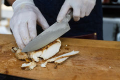 Closeup of the hands of a butcher cutting slices of meat off a l stock photo