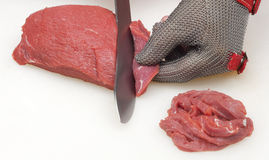 Closeup of the hands of a butcher cutting slices of raw meat off a large loin Stock Image