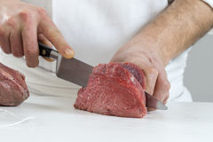 Closeup of the hands of a butcher cutting slices of raw meat off a large loin for tournedos Stock Photo