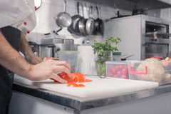 Closeup hands chef kitchen, cutting tomatoes royalty free stock image