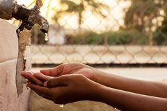 Closeup of hands, child drinking water directly from corporation tap water in India royalty free stock photos