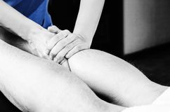 Closeup of hands of chiropractor/physiotherapist doing calf musc. Le massage to man patient,  in silhouette studio Stock Photography