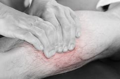 Closeup of hands of chiropractor/physiotherapist doing calf musc. Le massage to man patient,  in silhouette studio. Red color pain Stock Image