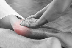 Closeup of hands of chiropractor/physiotherapist doing calf muscle massage to man patient, in silhouette studio. Red color pain. stock photo