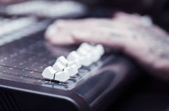 Closeup of hands covered with tattoos working on mixer console, pushing faders, studio equipment concept Stock Photos